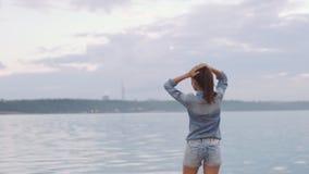 Härlig flicka på banken av floden som poserar på kamera lager videofilmer