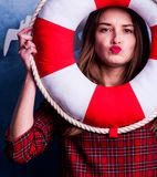 Härlig flicka på en blå bakgrund med en väldoftande röd cirkel Marin- design royaltyfria foton