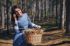 Härlig flicka på en cykel som talar på telefonen, med mörkt hår och hatten som står nära cykeln med korgen Attraktiv ung kvinna i Royaltyfri Bild