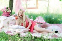 härlig flicka på en picknick i träna Arkivfoto