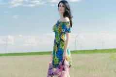Härlig flicka på fältet med väderkvarnar i bakgrunden Royaltyfri Fotografi