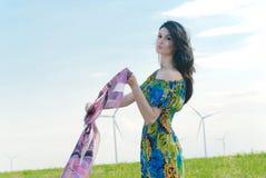 Härlig flicka på fältet med väderkvarnar i bakgrunden Arkivbild