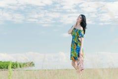 Härlig flicka på fältet med väderkvarnar i bakgrunden Arkivfoto