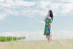Härlig flicka på fältet med väderkvarnar i bakgrunden Arkivbilder
