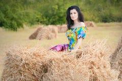 Härlig flicka på fältet mellan baler av sugrör Arkivbild