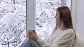 Härlig flicka på sammanträdefönsterbrädan som dricker te och ser fönstret utvändig vinter arkivfilmer