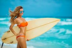 Härlig flicka på stranden med surfingbrädan Arkivbilder