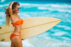 Härlig flicka på stranden med surfingbrädan Royaltyfria Foton