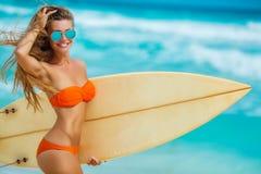 Härlig flicka på stranden med surfingbrädan Arkivbild