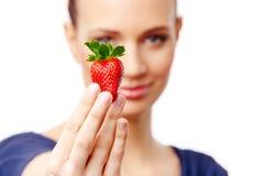 Härlig flicka på vit bakgrund som rymmer en jordgubbe Royaltyfri Fotografi