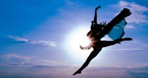 Härlig flicka som är tonårig i gymnastiskt hopp mot blå himmel Arkivbild