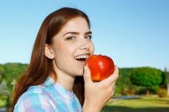 Härlig flicka som äter äpplet i parkera royaltyfria bilder