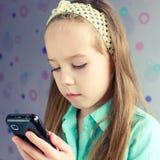 Härlig flicka som använder mobiltelefonen Arkivbilder