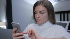 Härlig flicka som använder Smartphone, medan sitta i sovrum arkivbild