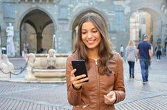 Härlig flicka som använder smartphonen i stads- bakgrund Royaltyfri Fotografi