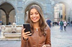 Härlig flicka som använder smartphonen i stads- bakgrund Arkivfoto