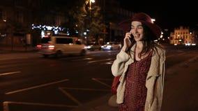 Härlig flicka som använder smortphone på gatan på natten arkivfilmer