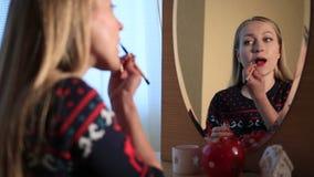 Härlig flicka som applicerar läppstift med målarfärg-borsten arkivfilmer