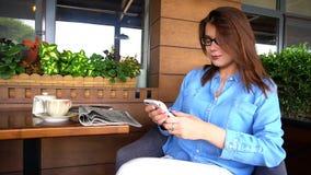 Härlig flicka som arbetar med den smarta telefonen på restaurangen in royaltyfri fotografi