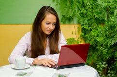 Härlig flicka som arbetar på den utomhus- anteckningsboken Arkivfoton