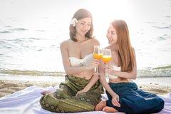 Härlig flicka som bär den thailändska klänningen som sitter på stranden royaltyfri foto