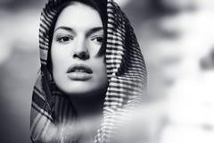 Härlig flicka som bär en halsduk, stående som är svartvit Royaltyfri Bild