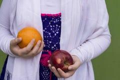 Härlig flicka som bär traditionellt stuckit hållande äpple a för torkduk royaltyfri fotografi