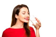 Härlig flicka som dricker ett exponeringsglas av rent vatten som ler att rymma Fotografering för Bildbyråer