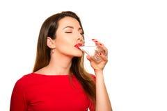Härlig flicka som dricker ett exponeringsglas av rent vatten som ler stängande Ey Arkivfoton