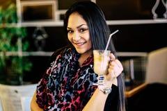 Härlig flicka som dricker ismockaskakan i ett kafé Arkivbild