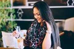 Härlig flicka som dricker ismockaskakan i ett kafé Arkivbilder