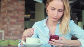 Härlig flicka som dricker kaffe och använder telefonen i ett kafé arkivfilmer