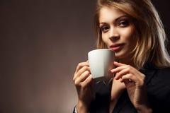 Härlig flicka som dricker te eller kaffe Fotografering för Bildbyråer