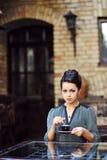 Härlig flicka som dricker te eller kaffe i kafé Arkivbild