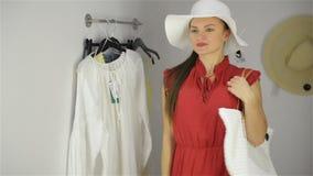 Härlig flicka som försöker den nya handväskan nära spegeln på provhytt Ung kvinna som b?r den roliga hatten Lyckligt shoppingbegr lager videofilmer