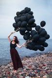 Härlig flicka som går med svarta ballonger Fotografering för Bildbyråer