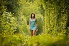 Härlig flicka som går till och med naturtunnelen Arkivbild