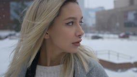 Härlig flicka som går till och med staden i vinter arkivfilmer