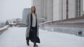 Härlig flicka som går till och med staden i vinter lager videofilmer