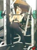 Härlig flicka som gör övningar i idrottshallen arkivbild