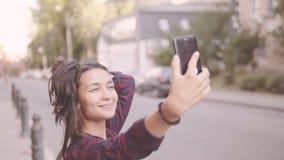 Härlig flicka som gör selfie, medan gå runt om staden lager videofilmer