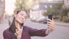 Härlig flicka som gör selfie, medan gå runt om staden stock video
