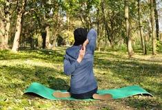 Härlig flicka som gör yoga på parkera på en solig dag Arkivbild