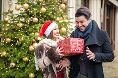 Härlig flicka som ger gåva till pojkvännen för chritsmas Fotografering för Bildbyråer