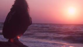 Härlig flicka som håller ögonen på rosa solnedgång på havet av mörk färg som sitter på en sten lager videofilmer