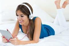 Härlig flicka som hemma lyssnar till musik med minnestavlan på soffan Royaltyfria Bilder