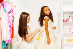 Härlig flicka som hjälper hennes vän att passa klänningen Royaltyfri Fotografi