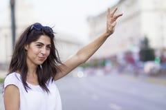 Härlig flicka som kallar taxitaxin Arkivfoto
