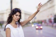 Härlig flicka som kallar taxitaxin Arkivbilder