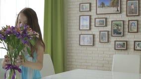 Härlig flicka som kommas med i gåvabukett av blommor lager videofilmer